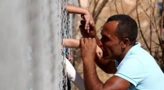 بعد عام من الفراق.. أسرة سورية تتبادل القبلات عبر سياج في قبرص