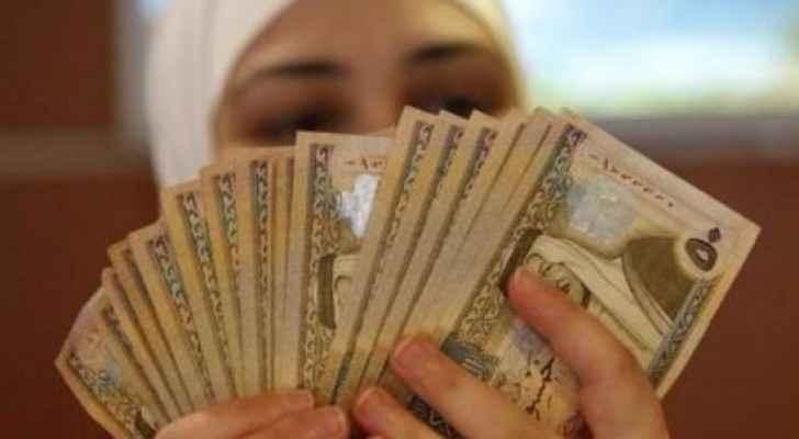 موظفة تعد أوراق نقد من الدينار الأردني