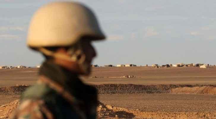 جندي بقوات حرس الحدود الأردني خلفه يظهر مخيم الركبان داخل سوريا - أرشيف