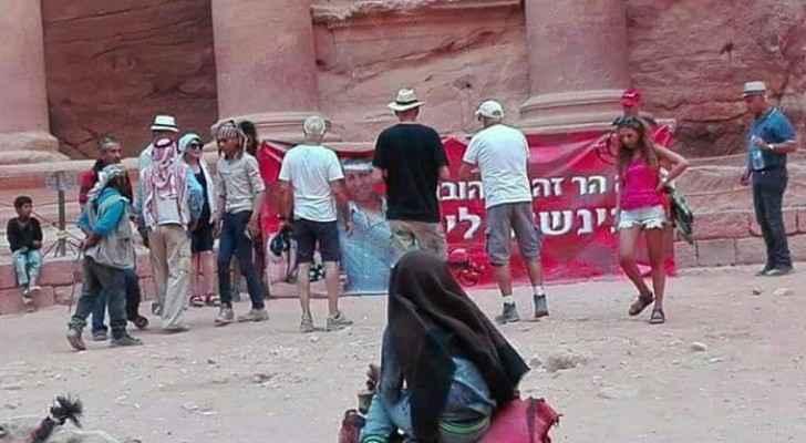 سياح إسرائيليين يرفعون يافطة أمام خزنة البترا