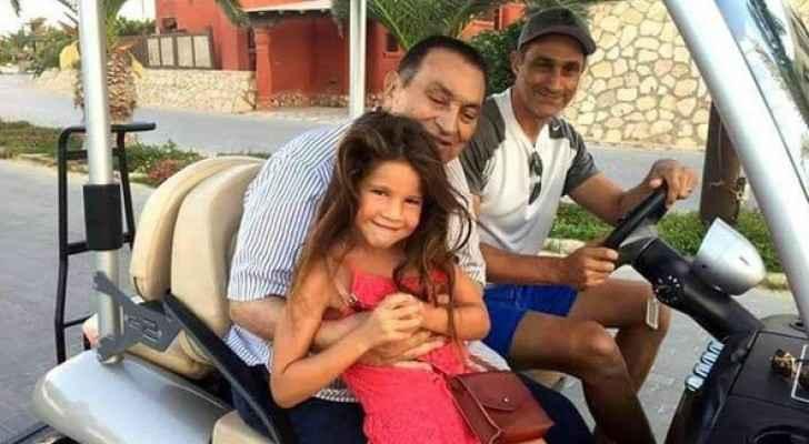 مبارك يحمل حفيدته وبجوارهما نجله جمال