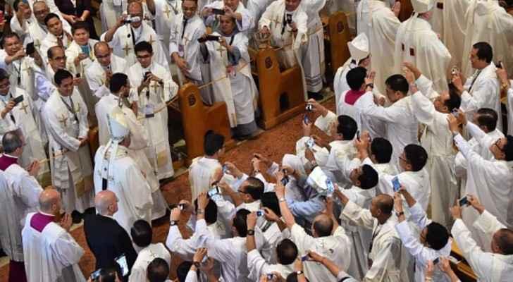 قساوسة يلتقوطون صورا للبابا فرنسيس خلال زيارة إلى الفلبين.