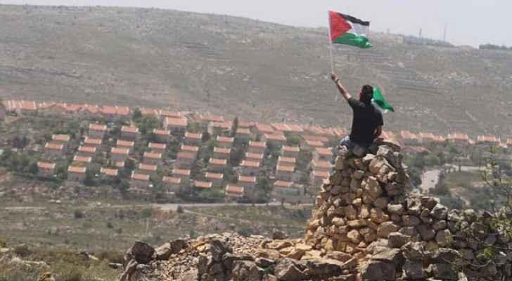 شاب يلوح بالعلم الفلسطيني أمام مستوطنات إسرائيلية- أرشيفية