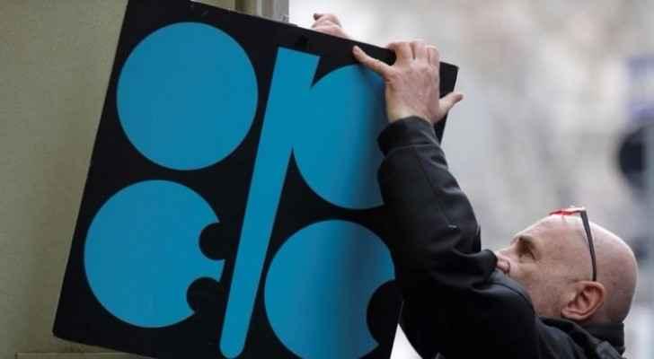 رجل يثبت شعار منظمة البلدان المصدرة للبترول (أوبك) بجوار مدخل مقر المنظمة