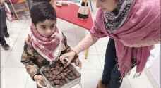 بالصور.. طفل كركي يقدم التمر عن روح الشهيد المعايطة