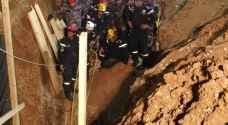 الدفاع المدني ينتشل احدى جثتي انهيار حفرة القويسمة