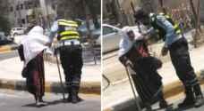 رجل أمن يساعد احدى المسنات لقطع الطريق - صورة