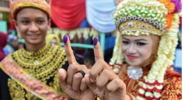 ناخبان إندونيسيان بعد الإدلاء بصوتيهما في مركز اقتراع في ترومون