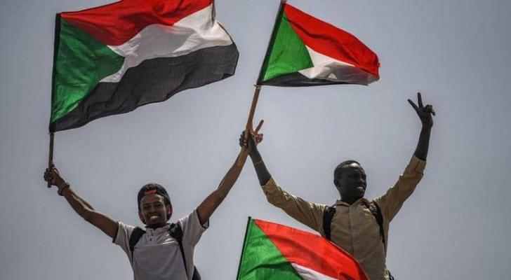 سودانيان يرفعان أعلام بلدهما
