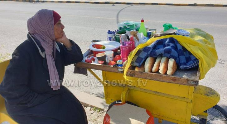 سيدة تنتظر رزقها على قارعة الطريق في عمّان