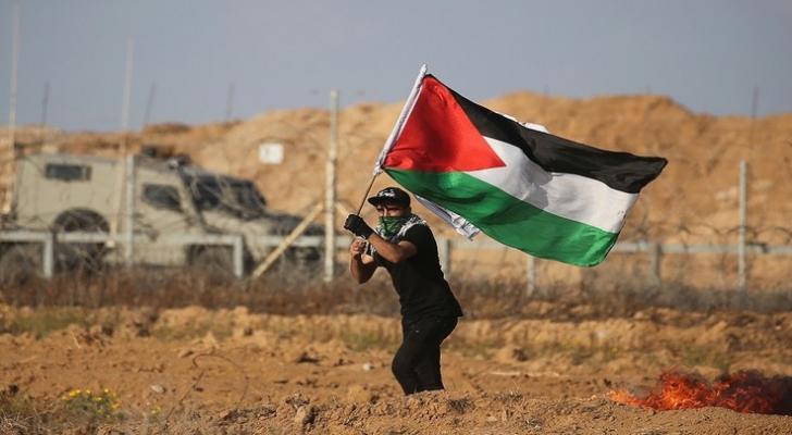 شاب فلسطيني يرفع علم بلاده