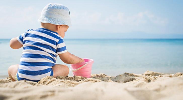طفل على الشاطئ تحت أشعة الشمس - الصورة تعبيرية