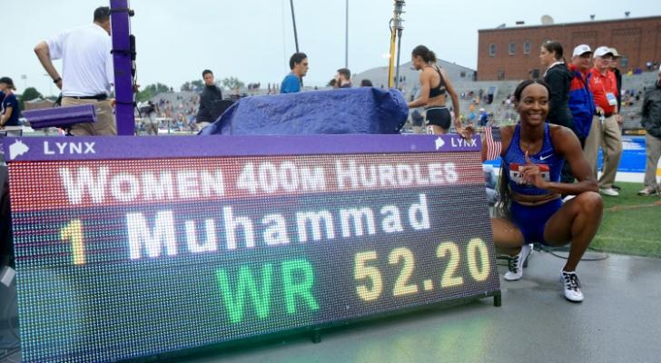 العداءة الامريكية دليلة محمد تلتقط صورة إلى جانب اللوحة الالكترونية التي تشير إلى رقمها القياسي العالمي في سباق 400 م حواجز والذي سجلته في بطولة الولا