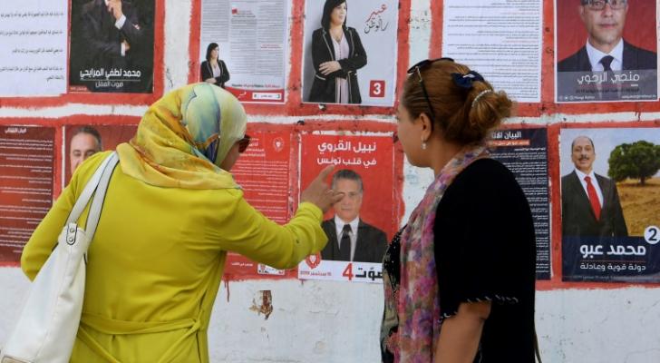 تونسيتان تنظران الى لافتات انتخابية