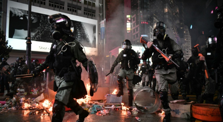 الشرطة تعبر قرب بقايا أشعلها متظاهرون في منطقة كوزواي باي في هونغ كونغ