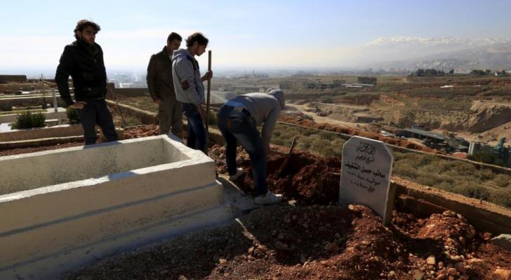 لاجئون سوريون يدفنون أحد موتاهم في سهل البقاع اللبناني