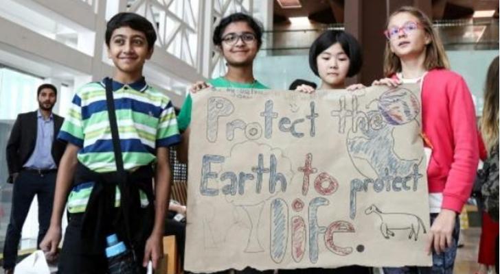 طلاب يرفعون لافتة تطالب بحماية الارض من التغير المناخي خلال وقفة احتجاجية في مقر المدينة التعليمية في قطر - ا ف ب