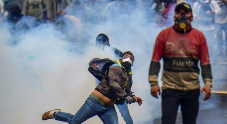 متظاهر يردّ قنبلة الغاز المسيل للدموع إلى الشرطة