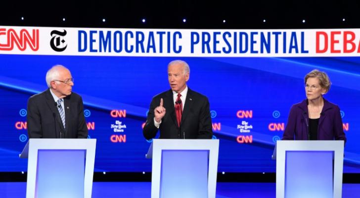 نائب الرئيس الأمريكي جو بايدن متوسطا المرشحان اليزابيث وارن وبيرني ساندرز خلال المناظرة