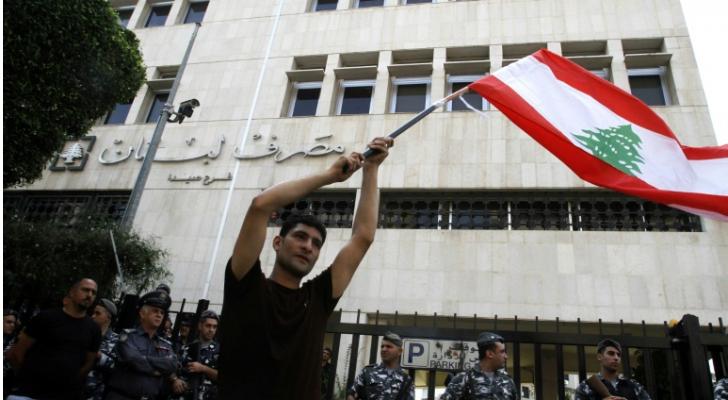 متظاهر يحمل العلم اللبناني خلال تظاهرة أمام المصرف المركزي فرع صيدا في جنوب لبنان في 28 تشرين الأول