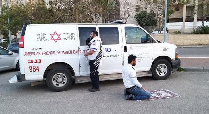 ممرضين يصليان أمام سيارة إسعاف أحدهما يهودي والآخر مسلم