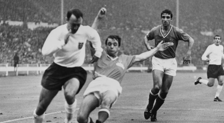 الهداف الإنكليزي جيمي غريفز يحاول مراوغة المدافع الفرنسي جاكي سيمون في مباراة المنتخبين في كأس العالم في 20 تموز/يوليو 1966