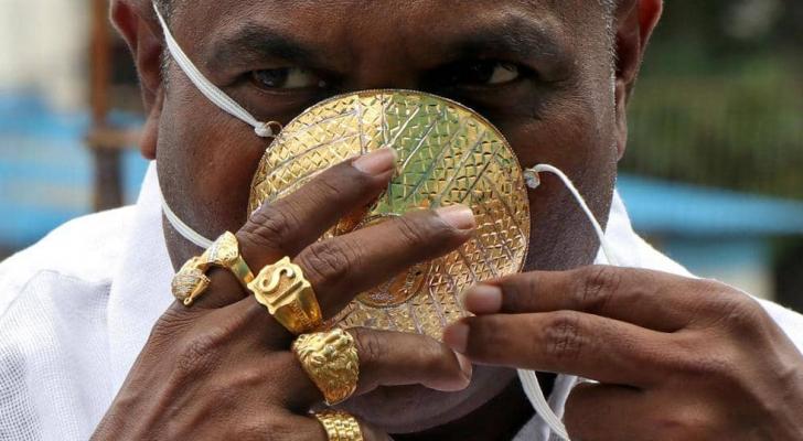 يضع رجل هندي كمامة مصنوعة من الذهب