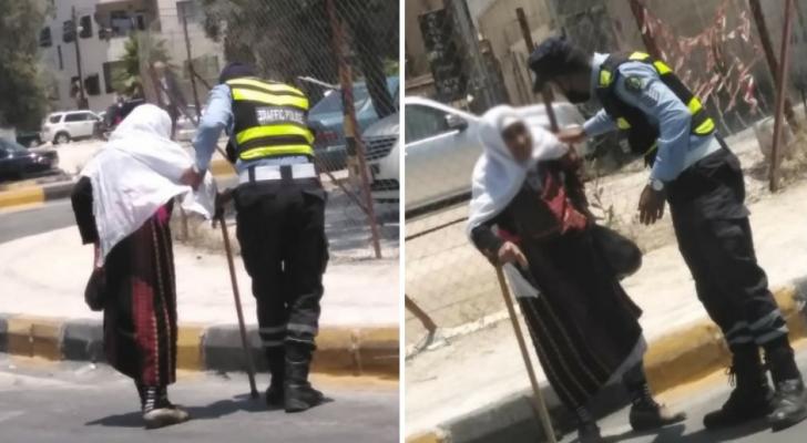 رجل أمن يساعد احدى المسنات لقطع الطريق